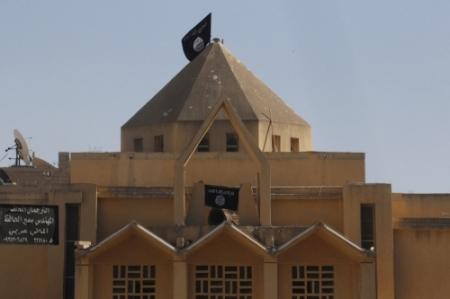 Bandeiras do Estado Islâmico do Iraque e da Síria são pendurados para substituir cruzes sobre a Igreja dos Mártires em ar-Raqqah (Reuters)