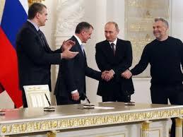 O presidente russo, Vladimir Putin, aperta a mão dos líderes da Crimeia e de Sevastopol após a assinatura do tratado que anexa a Crimeia à Rússia